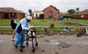 Onzelle Chandler makes her way out of her neighborhood after a tornado destroyed her home in the Dallas suburb of Lancaster, Texas.