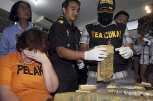 Indonesia custom officers observe drug evidence as British citizen Lindsay Sandiford, left, covers her face during a press conference in Kuta, Bali. Photo: AP