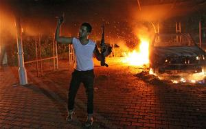 An armed man waves his rifle as buildings and cars are engulfed in flames after being set on fire inside the US consulate compound in Benghazi. Photo: Getty Images