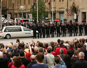 MELBOURNE, AUSTRALIA - MARCH 27:  Melbourne players, wearing the club blazers that Stynes had presented to them only days before he died, form a guard of honour as the hearse drives down Swanston Street during the State Funeral held for former AFL player Jim Stynes at St Paul's Cathedral on March 27, 2012 in Melbourne, Australia.  (Photo by Scott Barbour/Getty Images)