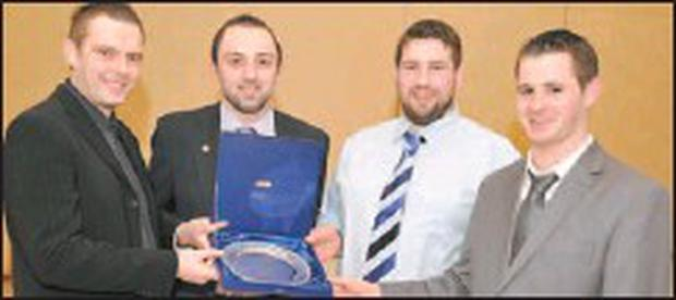 Cullen GAA's Diarmuid O'Connell makes a presentation to Gerard O'Leary, DJ Collins and Andrew O'Sullivan as an appreciation towards applying medical aid to him at a game during 2009.