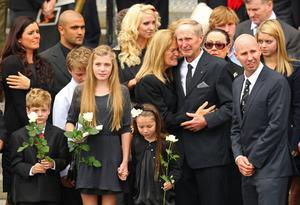 Family and relatives watch as the coffin is loaded into the hearse Photo: Getty Images