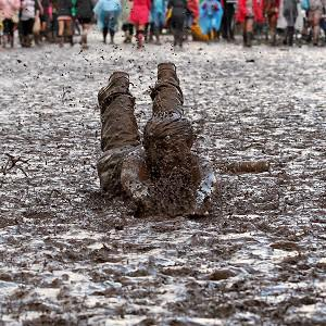 Chris Cameron from Glasgow mud dives at the T in the Park music festival at Balado Park near Kinross