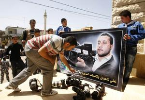 Colleagues laying down cameras in front of a portrait of the Lebanese cameraman Ali Shabaan at his funeral in the village of Maifadoun. Photo: Getty Images