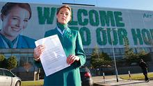 IMPACT cabin crew member Aideen Walsh standing in front of her picture for an Aer Lingus promotional poster at the company's Dublin Airport HQ yesterday. Ms Walsh is holding the letter given to her by management regarding her attendance at a disciplinary meeting