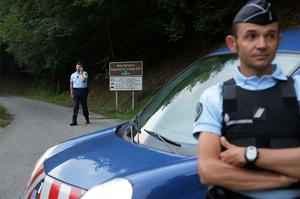 Gendarmes block access to the killing site near Chevaline, French Alps
