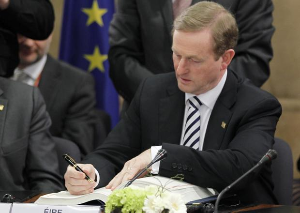 Irish Prime Minister Enda Kenny signs the Treaty on Stability, Coordination and Governance in the Economic and Monetary Union during an EU Summit in Brussels on Friday, March 2, 2012. The leaders of 25 European states have signed a new treaty designed to prevent the 17 euro countries from running up huge debts in order to prevent a repeat of the current crisis afflicting the single currency zone. Of the 27 European Union states, only Britain and the Czech Republic decided not to sign the treaty. (AP Photo/Francois Lenoir, Pool)