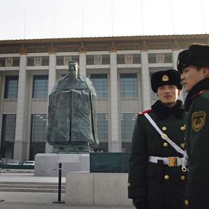 Chinese policemen in front of a sculpture of ancient philosopher Confucius which has now mysteriously disappeared