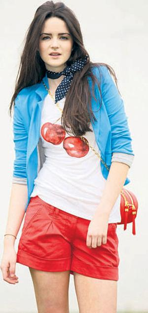 Blue blazer, €48; white cherryprint T-shirt, €24; coral shorts, €46; navy polka-dot neckerchief, €14.50; coral-and-gold quilted bag, €30, all Therapy