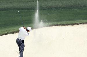 Tiger Woods blasts out of a bunker on the 8th hole during his third round at Augusta yesterday. Photo: Jamie Squire