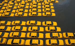 A parking lot full of yellow cabs is flooded as a result of superstorm Sandy in Hoboken, New Jersey. Photo: AP