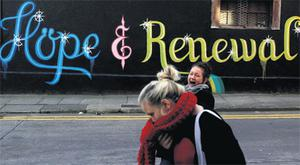 Students walk past graffiti on the side of a building in Dublin yesterday afternoon