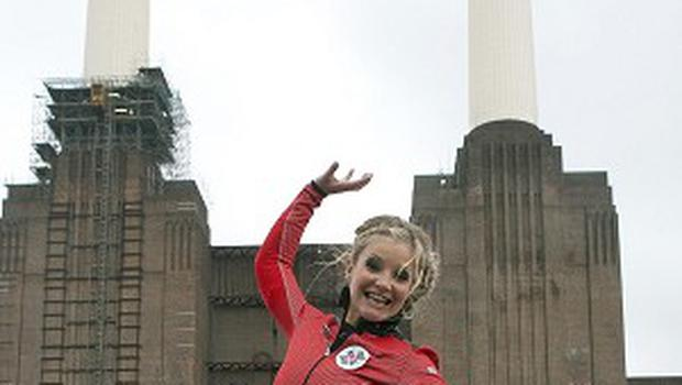 Helen Skelton celebrates after walking on a tightrope between two of the chimneys at Battersea Power Station