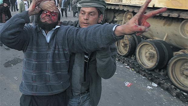 An injured anti-government protester is helped during clashes in Tahrir Square