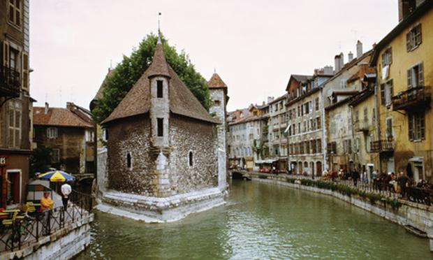 People walking by shops alongside river, Annecy, France.