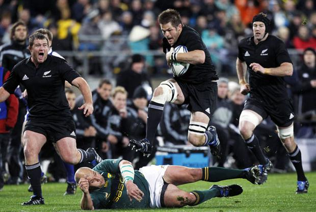 Richie McCaw jumps over CJ van der Linde during during yet another marauding All Blacks attack in Wellington. Photo: Reuters