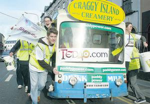 Dermot Morgan's son Bobby helps push the Father Ted milkfloat as it arrives in Galway's Eyre Square yesterday at the end of a 900-mile tour of the country in aid of Down Syndrome Ireland