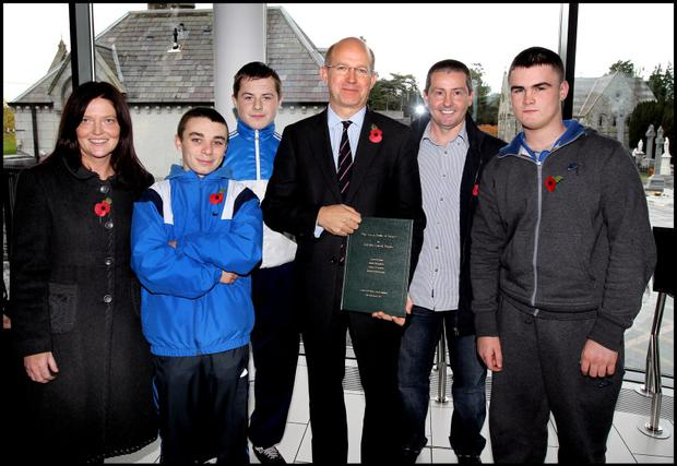 The British Ambassador to Ireland Mr Dominick Chilcott is presented with a commentary on the song WIllie Mc Bride The Green Fields of France by St pauls YEP Finglas students and teachers including from left, Nora Kielty(teacher), Aaron Boylan, Jamie Broughan, Principal David Carter and Michael Mc Donagh after laying weaths at Glasnevin Cemetarys Monument to the Two World Wars as the final 104 of 205 previously unmarked graves of Irish men and women who served the British and Commonwealth forces in the two World Wars were commemorated at a ceremony yesterday.Pic Steve Humphreys9th November 2012.
