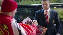 Wayne Rooney stops to give an autograph as he arrives at the UEFA headquarters in Nyon, Switzerland