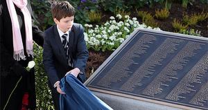 Jack Martin 12, a descendant of Dr John Simpson who perished on the Titanic, unveils a plaque in the new memorial garden at Belfast City Hall
