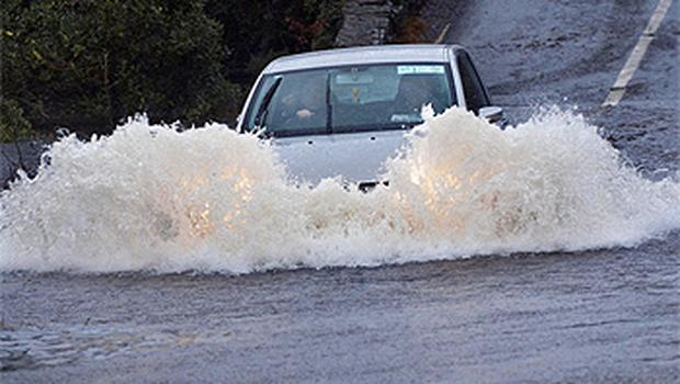 A car is driven through the flooded N71 in Kerry, which was later closed