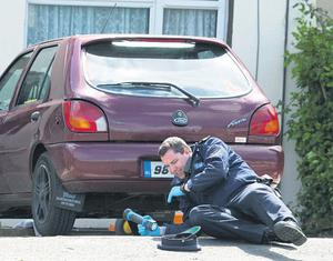 A car at the scene is forensically examined