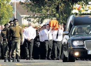 THEY HAVEN'T GONE AWAY YOU KNOW : Onlookers at the funeral of Alan Ryan yesterday were shocked to see a paramilitarystyle display with masked men in full military garb accompanying the coffin as it made its way through a north Dublin suburb.