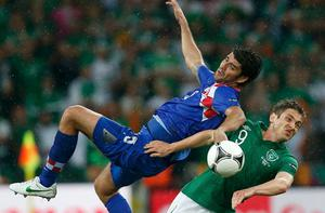 Croatia's Vedran Corluka (L) and Ireland's Kevin Doyle fight for ball