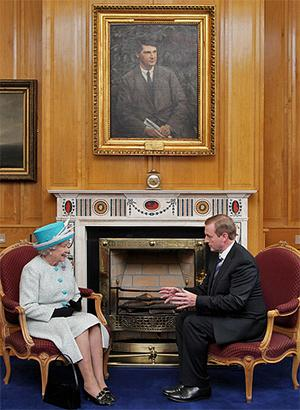 Queen Elizabeth and Taoiseach Enda Kenny talk in his office, as they sit under a portrait of Michael Collins. Photo: PA