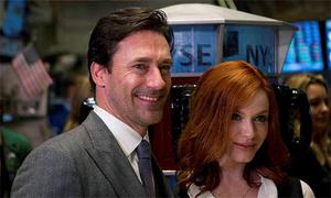 Actors Jon Hamm and Christina Hendricks from the series Mad Men smile while visiting the New York Stock Exchange to ring the opening bell in New York, March 21, 2012.