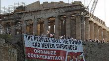 Protesters from the Greek Communist-affiliated trade union PAME hold a huge banner in front of the Parthenon at the Acropolis hill.