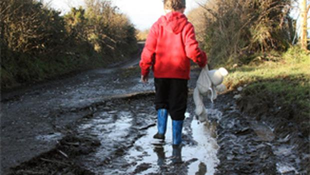 A boy makes his way along a damaged road on the outskirts of Cootehill, Co. Cavan