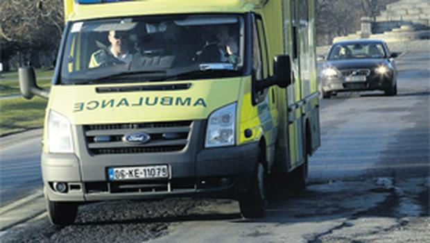 An ambulance tries to avoid some of the dozens of potholes littering Chesterfied Avenue – the main road through the Phoenix Park – outside Arus an Uachtarain in Dublin yesterday