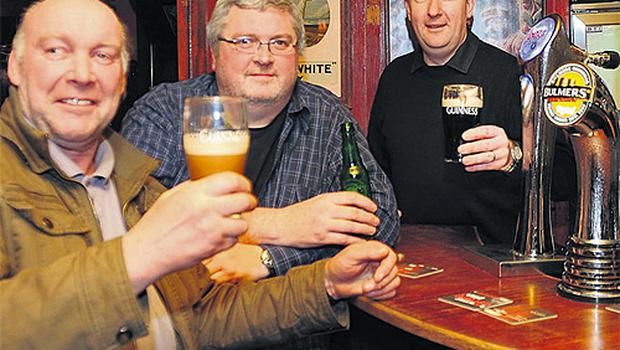Paul Bell, right, owner of the Brewery Tap Bar, Tullamore, Co Offaly, with Brian Cowen supporters Kevin Molloy and Ciaran Duffy as they awaited the result of the vote yesterday