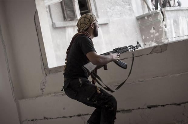 a rebel fighter prepares to fire on pro-government forces in the Karm al-Jebel neighborhood of Aleppo. Photo: AP