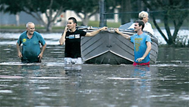Local business owners walk their boat down a street in a commercial area of Brisbane yesterday