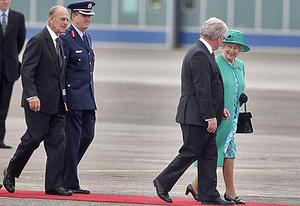 Queen Elizabeth II and Tanaiste Eamon Gilmore, followed by the Duke of Edinburgh, walk along the red carpet at Casement Aerodrome. Photo: PA