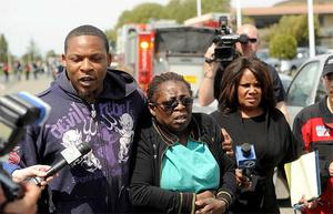 Marilyn Daniels, center, an employee at Oikos University, is comforted near the school in Oakland, Calif. Photo: AP
