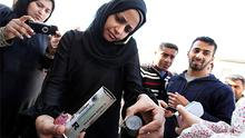 A woman shows empty packages of rubber baton rounds and sound bombs used by riot police in Manama, Bahrain yesterday. Photo: Reuters