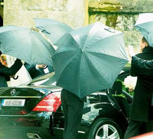 Bride Nivek is shielded by umbrellas as she emerges from a black Mercedes. Photo: Gerry Mooney