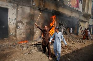 A protester holds a stick as he shouts anti-American slogans in front of a burning cinema during an anti-US protest rally to mark the 'Day of Love' in Peshawar