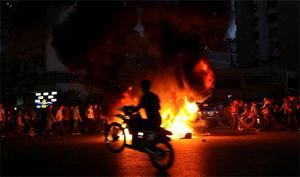 A man rides his scooter past tires set on fire by Lebanese Shi'ite Muslims blocking a street in Beirut to protest the kidnapping of Lebanese Shi'ite men in the northern Syrian city of Aleppo. Photo: Reuters