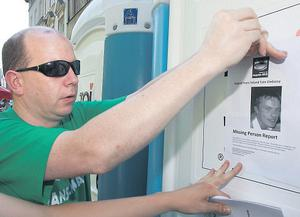 Gareth Mullen putting up posters in Poznan