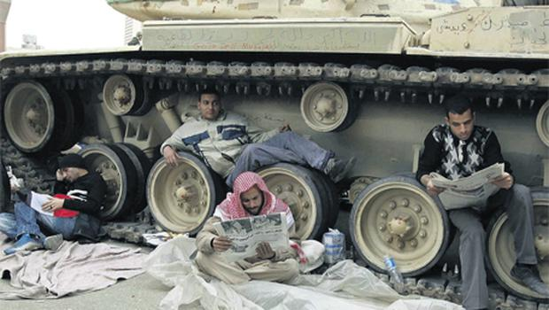 Anti-government protesters rest by an Egyptian army tank in Tahrir Square, Cairo, yesterday. Photo: Reuters