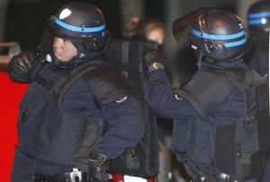 French police officers wait next to the building in Toulouse, France, Wednesday March 21, 2012 where a suspect in the shooting at the Ozar Hatorah Jewish school has been spotted. A father and his two sons were among four people who died Monday when a gunman opened fire in front of a Jewish school in the city in southwest France. (AP Photo/Bob Edme)
