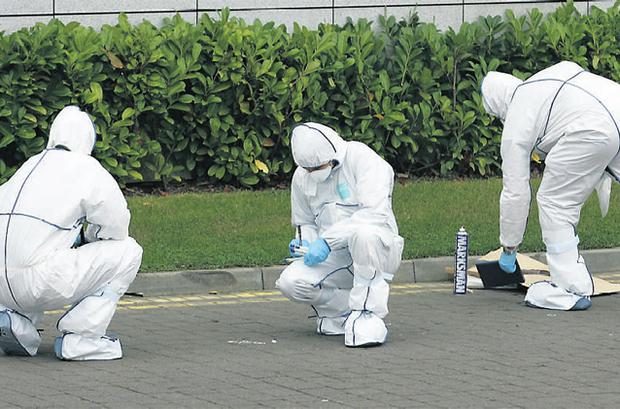 Garda forensic officers examine the scene of the fatal brawl outside Hannigen's pub in Park West in Dublin yesterday