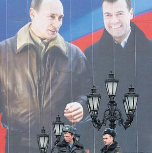 UNITED FRONT: Moscow police stand in front to a poster of Vladimir Putin and his approved successor Dmitry Medvedev
