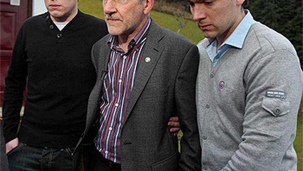 A devastated Mickey Harte outside the family home near Ballygawley, Co Tyrone yesterday with two of his sons Matthew (left) and Michael