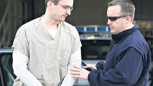 A US federal marshal escorts Niall Clarke to jail after he was sentenced for armed robbery