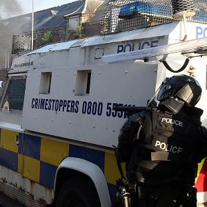 Police prepare to fire baton rounds after coming under petrol bomb attack from Nationalist youths in Ardoyne in north Belfast